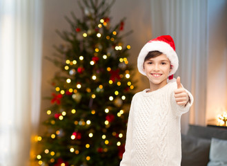 holidays, gesture, christmas, childhood and people concept - smiling happy boy in santa hat showing thumbs up over christmas tree lights background