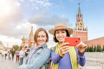 Two happy girls friends taking selfie on the Red Square with Kremlin tower at the background. Travel in Russia concept