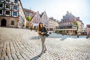 Young woman tourist walking on the beautiful city square in the old town of Nurnberg, Germany