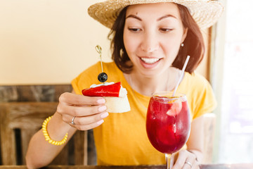 Young woman enjoying tasty traditional spanish snack tapas, with glass of sangria wine. Travel and Food in Spain concept