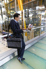 businessman in the airport with mobile phone and laptop