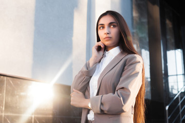 Young attractive girl in business suit at entrance of an office building