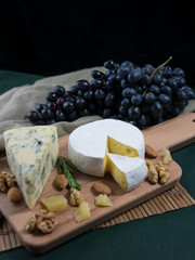 Variation of cheese, grapes and nuts on a wooden board