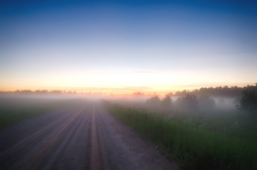 Beautiful morning sunrise landscape. Scenic Countryside landscape under a colorful sky at sunset dawn sunrise. Sunrise sky and the morning mist on the village road