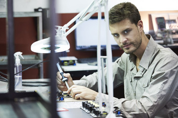 Portrait of engineer soldering circuit board in office