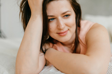 Beautiful brunette woman portrait luiyng on white bed at home in morning.  Female after waking up. Cheerful adult married blue eyed girl in pink nighty with positive face smiling and relaxing on sofa