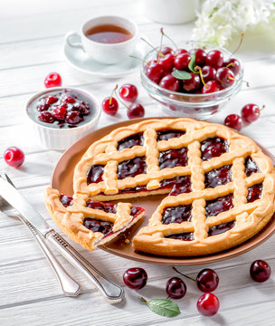 cherry tart on white wooden background served with fresh berries and cup of tea