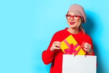 Portrait of a young girl in red sweater with gift box and shopping bag on blue background