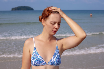 Girl having headache on seaside. Suffering woman on sunny beach. Woman sunstroke by sea. Hot sun danger.