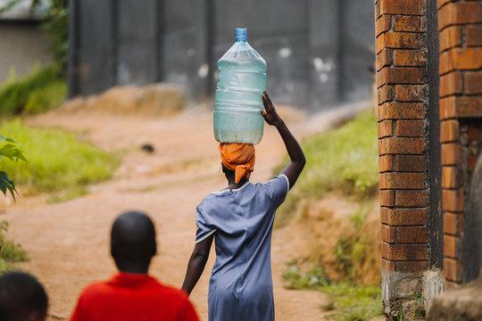 woman carrying water in Uganda, Africa