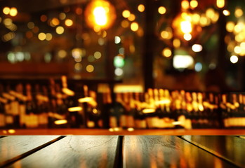 top of wood table with blur bottle of alcohol drinking for night party and colorful light of pub and bar background
