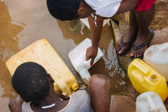 people getting water at a well in Uganda, Africa