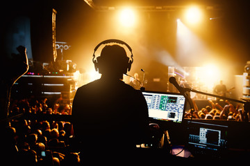 Club, disco DJ playing and mixing music for crowd of happy people. Nightlife, concert lights, flares