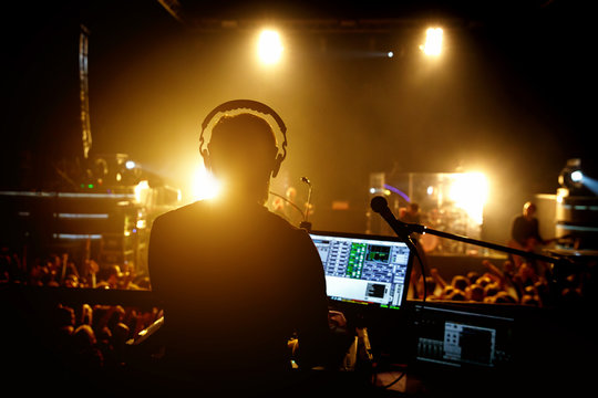 Sound engineer music producer adjusting and balancing audio on rock concert, silhouette opposite stage light