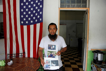 Benjamin Climaco poses with pictures of his brothers in his restaurant in San Salvador