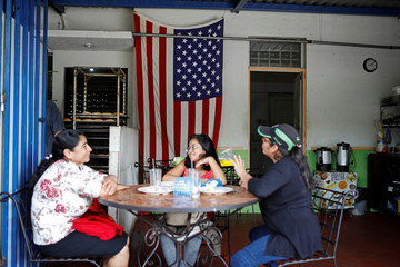 A U.S. flag hangs in the background as women rest after lunch in a family-owned restaurant in San Salvador