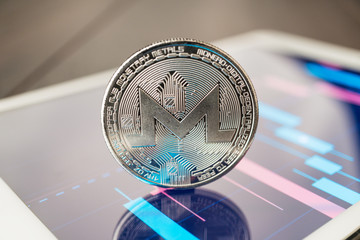 close-up photo of monero cryptocurrency physical coin on the tablet computer showing stock market charts. trading monero cryptocoin concept on the wooden table