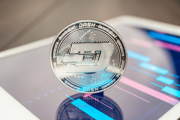 close-up photo of dash cryptocurrency also known as xcoin or darkcoin physical coin on the tablet computer showing stock market charts. trading dash cryptocoin concept on the wooden table