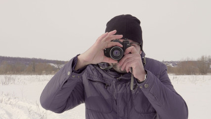 A man takes a picture. shoots on an old camera. Winter season. Warm clothing. Snow field. Bright day. Largest species. 4K video