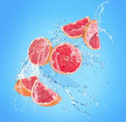 grapefruit slices in water splash on a blue background