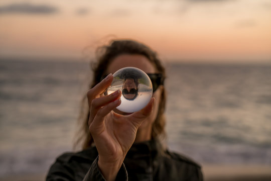 Girl holding a lens ball on the beach at sunset time