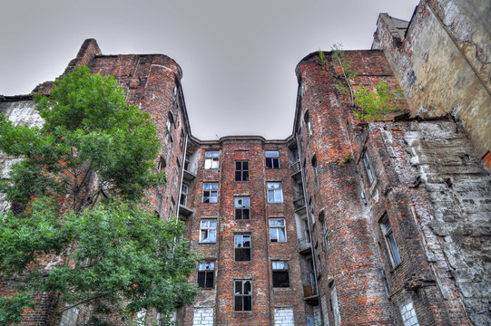 Facade of ruined old vintage red brick ghetto house at Kamienico, part of former Jewish ghetto, Warsaw city, Poland - HDR (High Dynamic Range) image