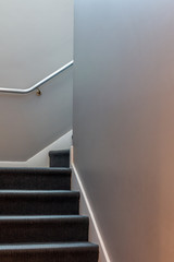 A narrow dark colored carpeted stairs leads upward to a landing and then turns right. A beige wall is on each side of the stairs. A banister in on the far wall leading to the next level.
