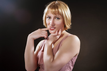 Portrait of Caucasian Blond Female in Pink Dress. Posing Against Black Background with Questioning Facial Expresison and Toching Teeth with Finger.