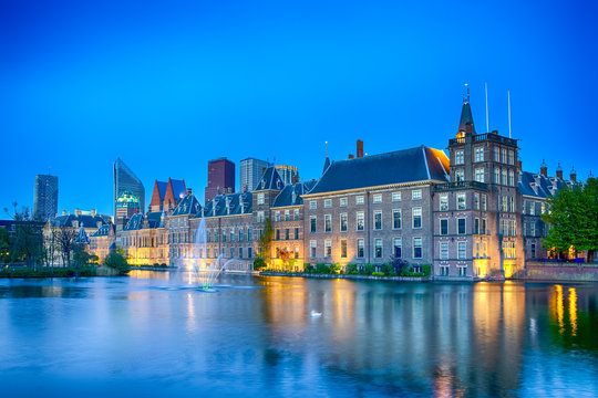 Travel Concepts. Binnenhof Palace of Parliament in The Hague in The Netherlands at Blue Hour. Against Modern Skyscrapers on Background.