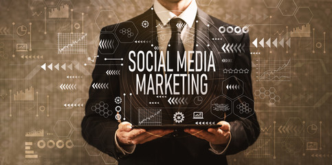 Social media marketing with businessman holding a tablet computer on a dark vintage background