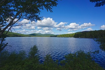 Adirondack Park, New York, USA: View of mountains in the distance from the shore of Sagamore Lake, with dramatic clouds overhead on a bright summer day.