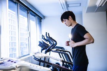 ランニングマシンに乗って体力を鍛える男性