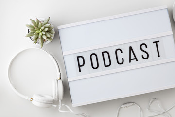 Podcast word on lightbox with headphones, coffee cup and notepad on white table