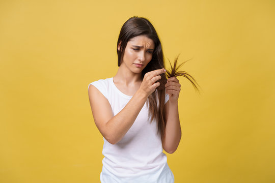 Woman hand holding her long hair with looking at damaged splitting ends of hair care problems.
