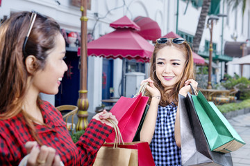 Smiling two asian woman with many shopping bags