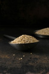 A low light image of a metal spoon and bowl of sesame seeds on a rustic background with copy space for your text