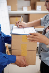 Delivery service manager signing document and taking parcels from courier