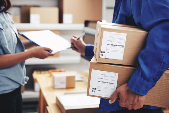 Courier with parcels signing document in delivery service office