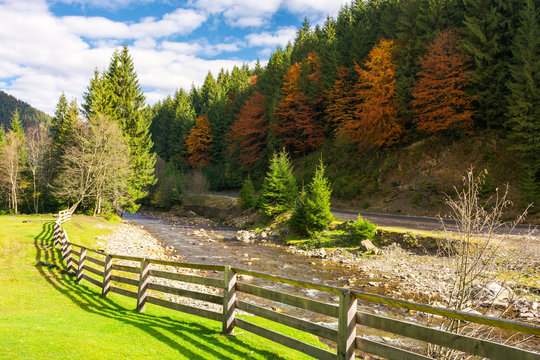 camping place near the river. wooden fence on a grassy lawn along the shore. road under the hill with trees in fall color. beautiful sunny autumn weather