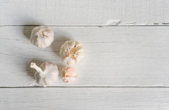 Organic garlic whole and cloves on white wood background.
