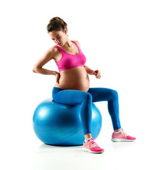 Lower back pain. Photo of pregnant woman holding her back in pain isolated on white background. Concept of healthy life