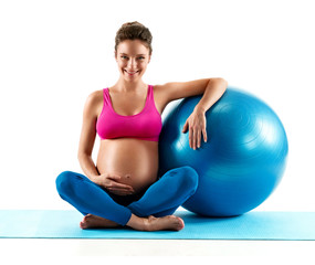 Smiling pregnant woman sitting with fit ball isolated on white background. Concept of healthy life