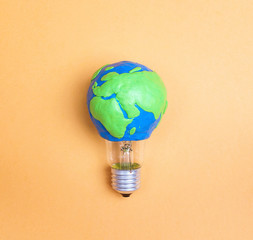 Light bulb with plasticine Earth planet model on yellow background. International Day of Energy Saving.