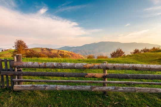 wooden fence on grassy rural field. distant mountain in morning haze. lovely autumn countryside