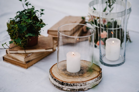Table for wedding ceremony is decorated with flowers, cage, candles, books and greens, greenery. Compositions of wedding wooden decor in the backyard banquet area. Close up. Artwork in style vintage.