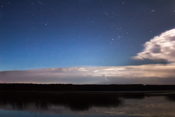 Clouds and stars above lake in the summer night before thunder