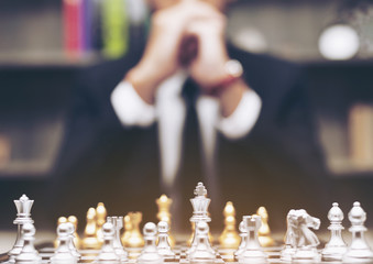 Businessman with clasped hands planning strategy play with chess game. ,blur. concept of business strategy and tactic to success