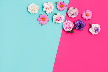 Bright colorful background with small artificial roses. Place for text. Flat lay.