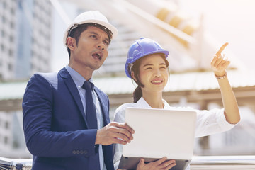 Two Asian engineers working or discussion on a building site and using laptop. Business people in safety helmet talk New Project or Product Details with Chief Engineering and architecture concept