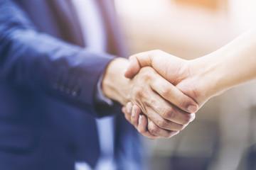 Concept of Negotiating business and handshake Gesturing People Connection Deal. close up hand of business man shaking hands with partner or customer on modern city background,fair play. film tone